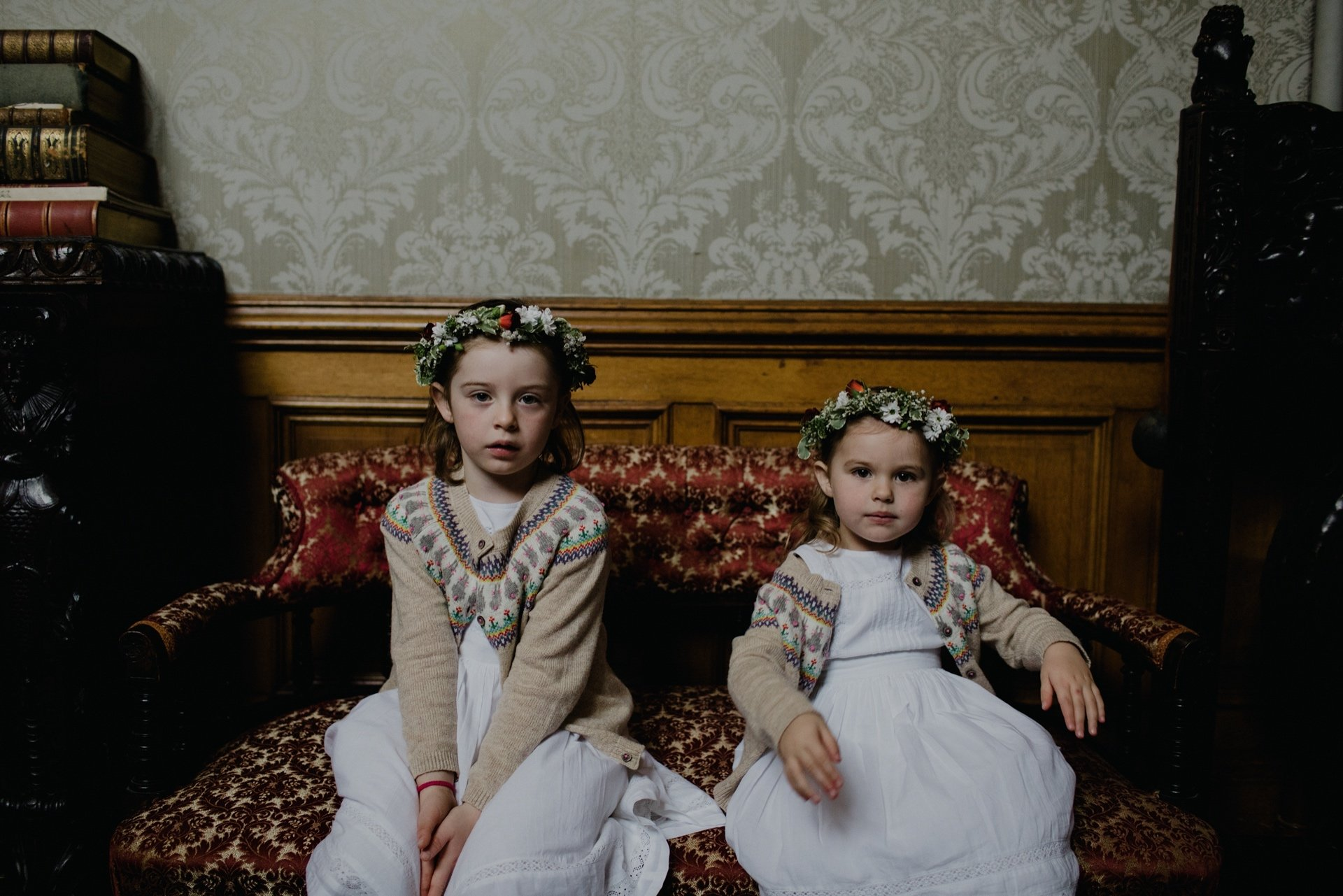flower girls relaxing on the sofa, girls wear cardigans and flower crowns with white dresses