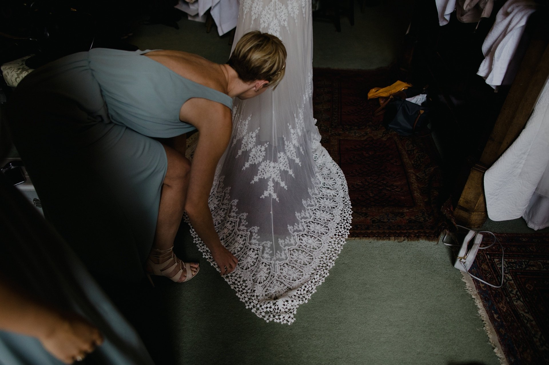 bridesmaid sorting train on wedding dress by dreamers and lovers