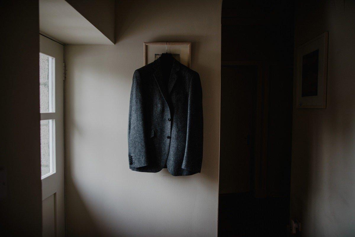 Groom's grey tweed jacket hanging in the window light