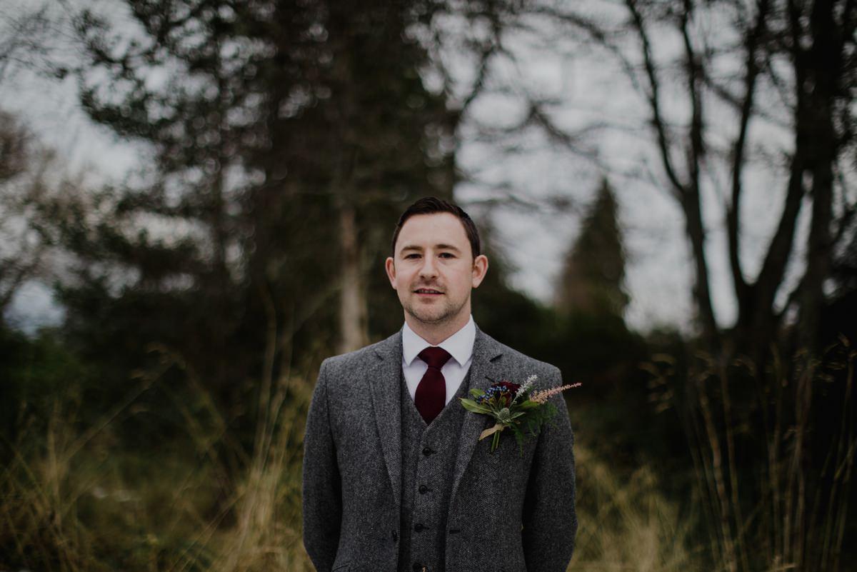Outdoor portrait of groom wearing grey tweed suit.