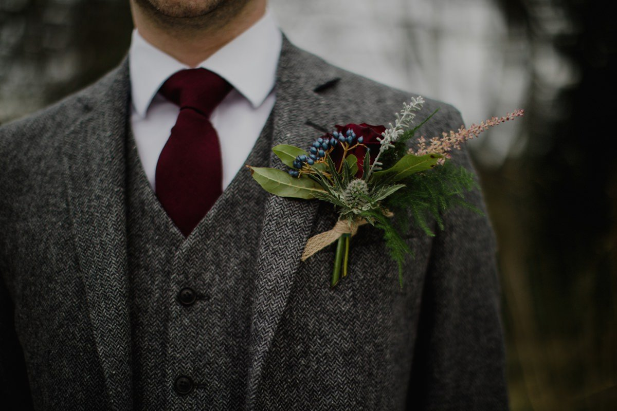 Detail of groom wearing his rustic buttonhole and tweed suit