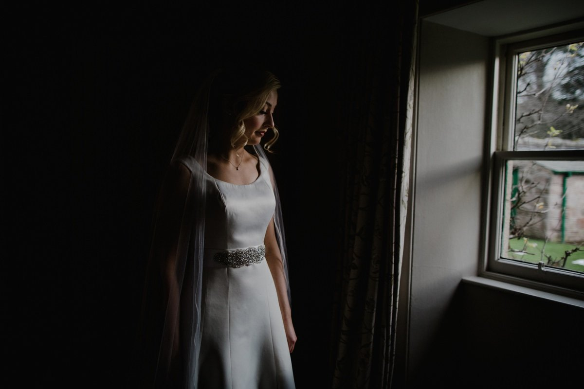 moody portrait of the bride in the window light