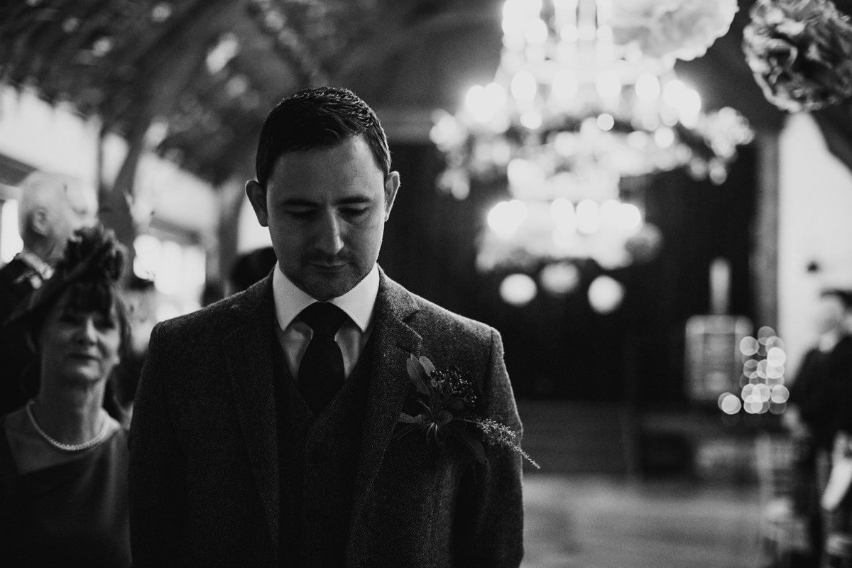 black and white of groom patiently waiting for his bride