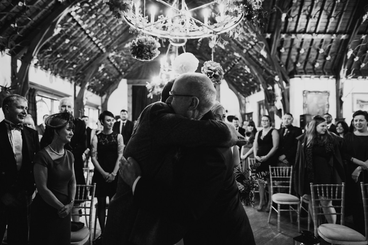 groom hugs father of the bride after walking her up the aisle to meet him
