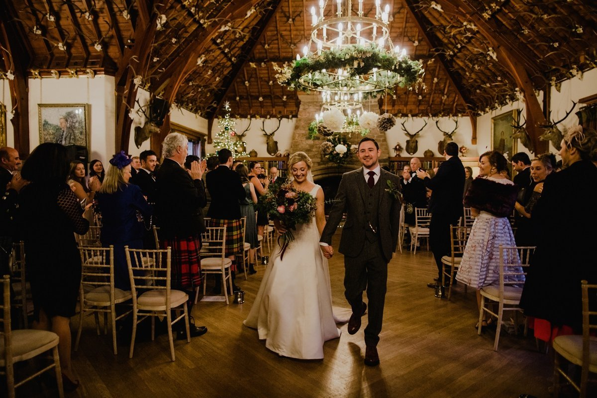Wedding couple walking down the aisle, now married at Glen Tanar Ballroom