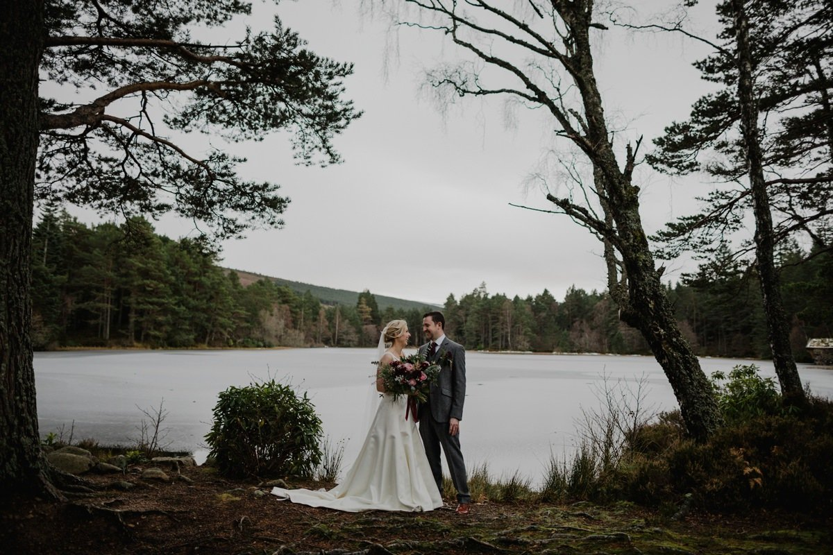 Bride and Groom Portrait by the loch at Glen Tanar framed by trees.