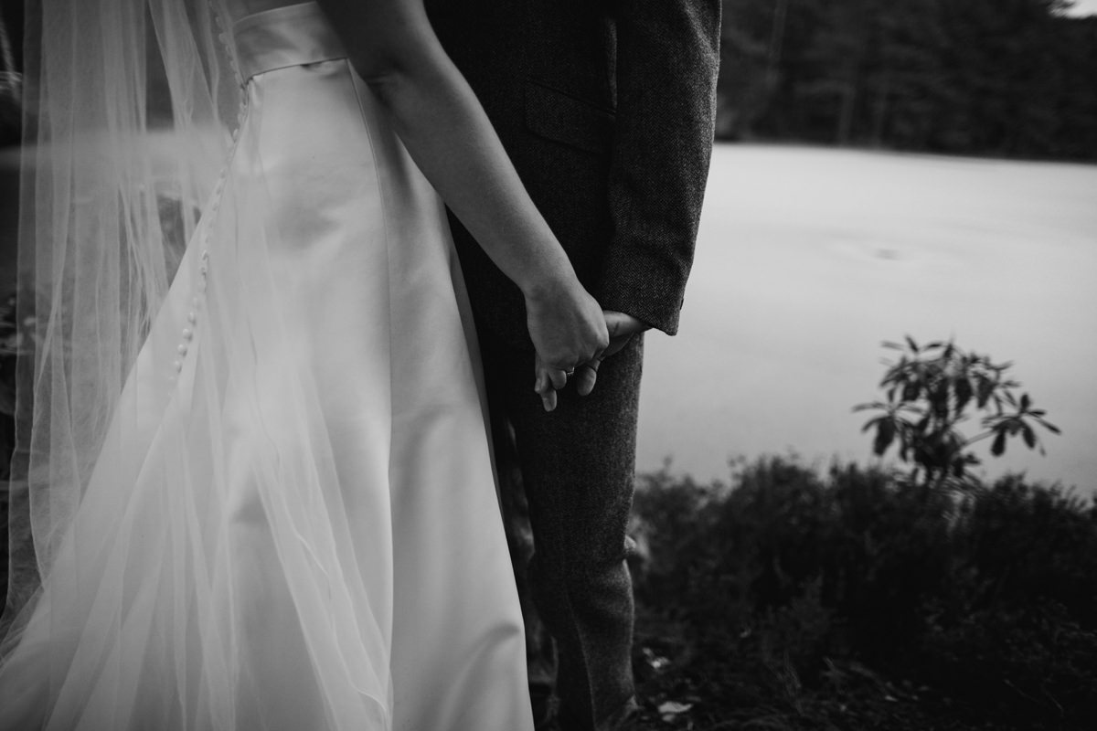 Black and White of bride and groom holding hands during their portraits