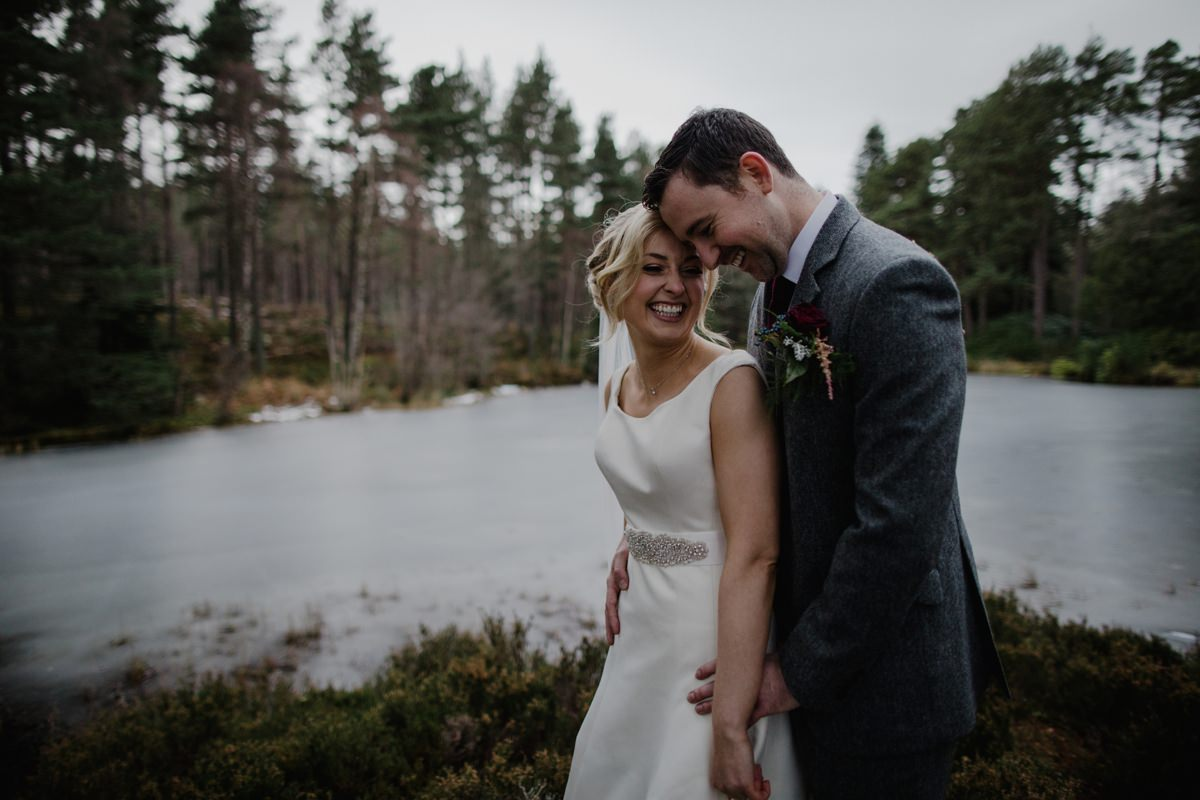Bride and Groom laughing at the frozen lochside