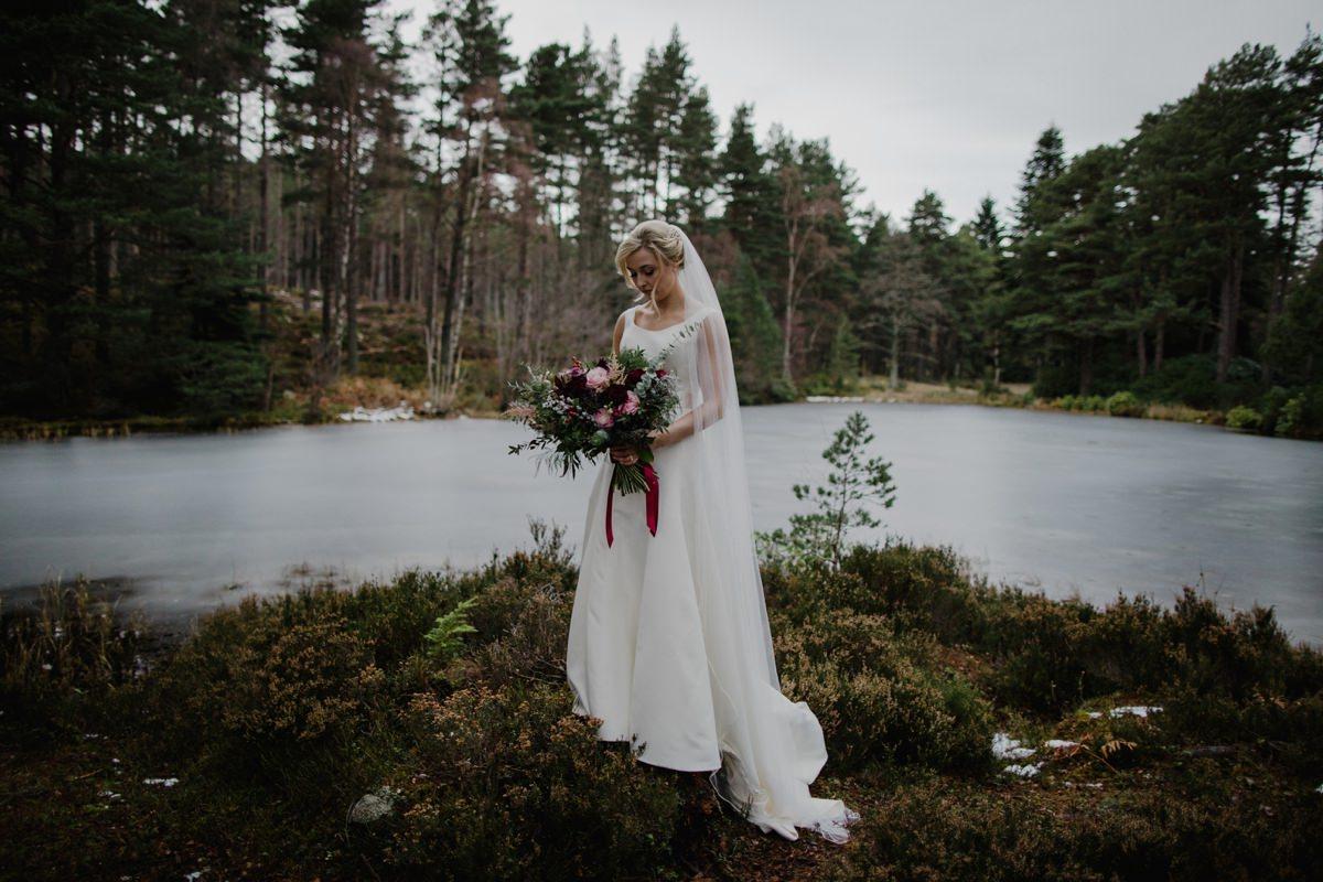 Bride at the frozen lochside gazing at her wild rustic bouquet