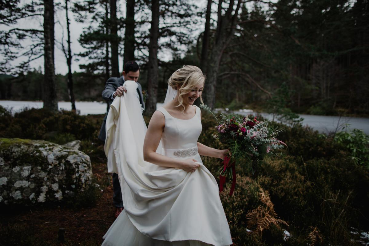 Groom helping with bride's dress as she walks in the woodland at Glen Tanar