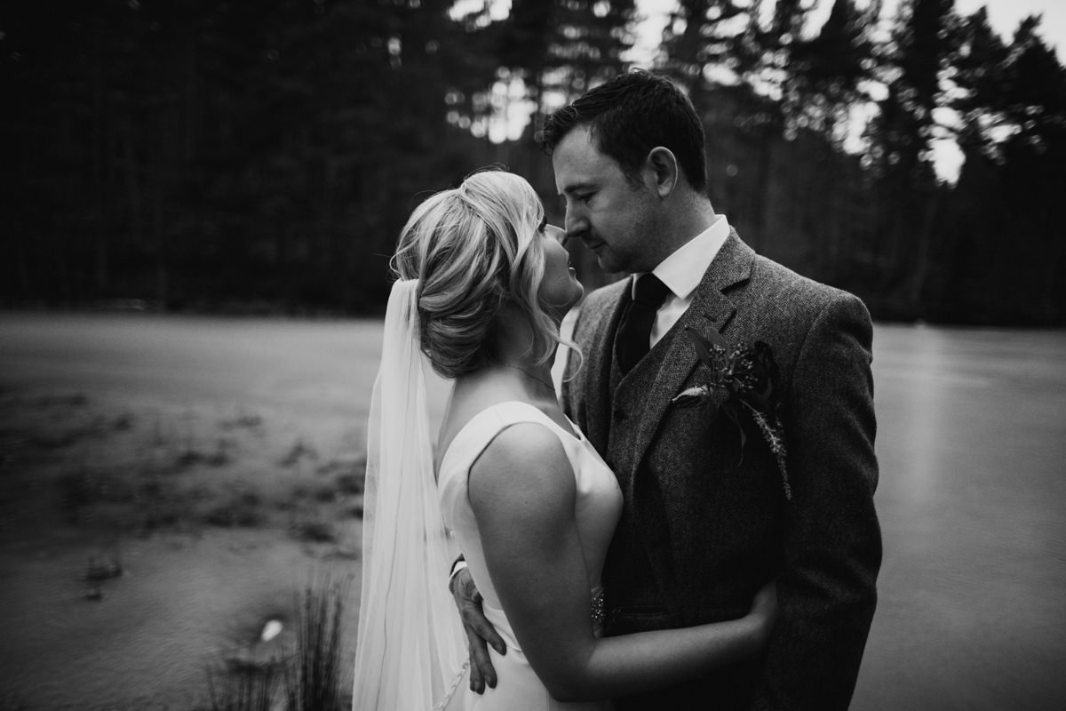 Black and White moody portrait of bride and groom by the frozen loch at Glen Tanar