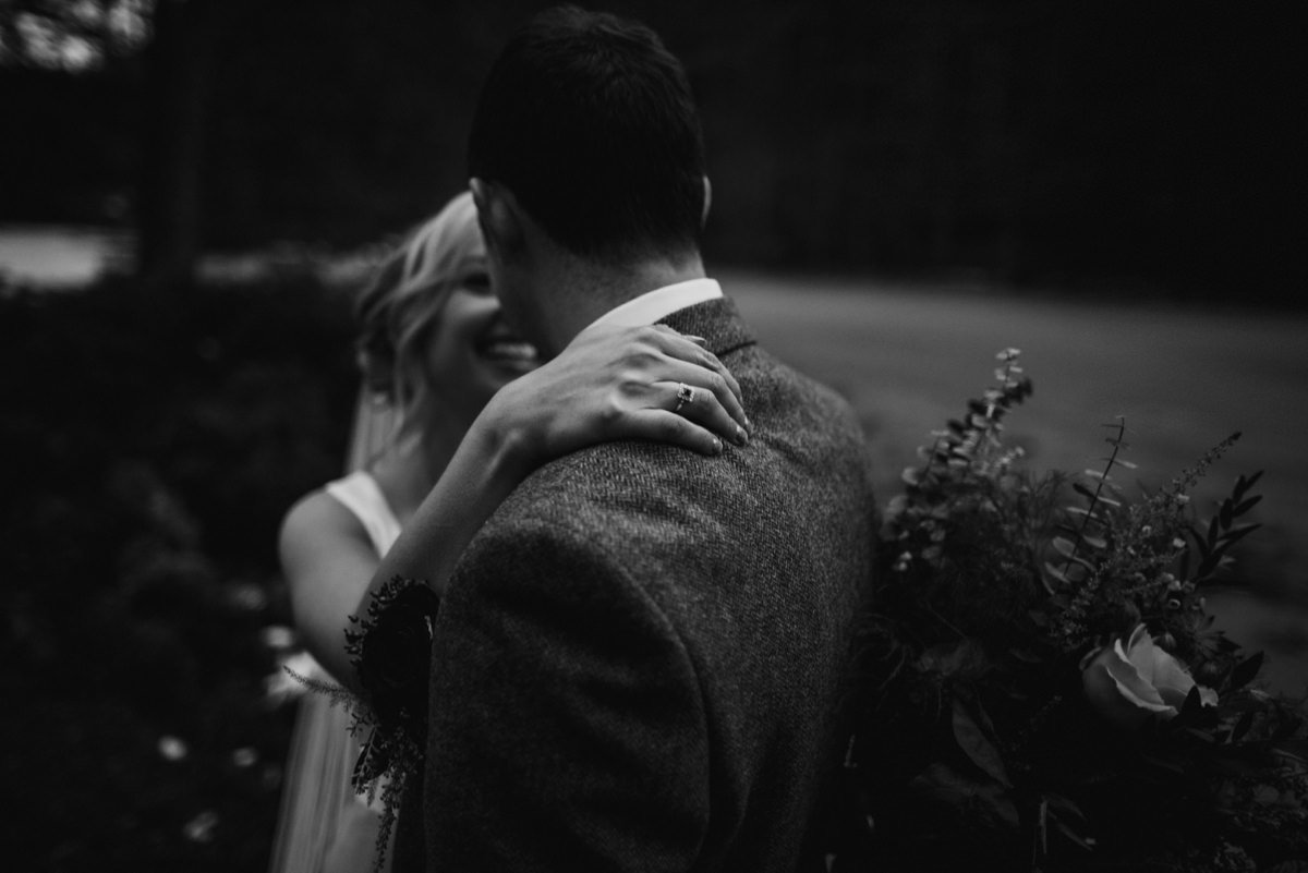 Black and white of bride's hand on groom's shoulder with ring detail