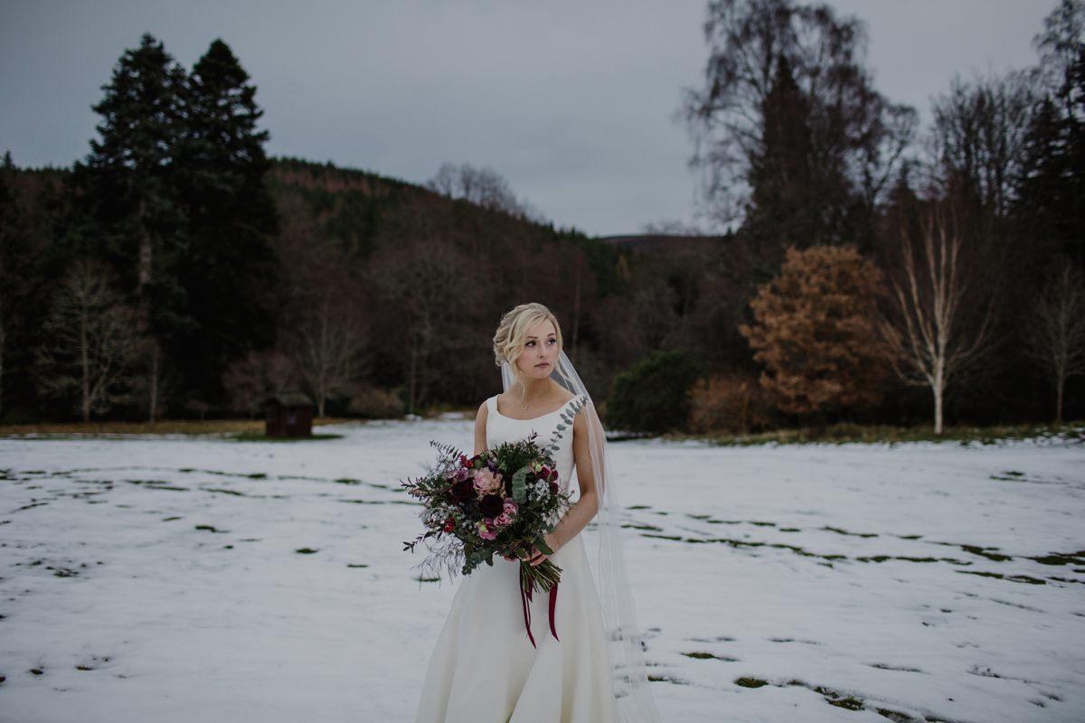 Portrait of bride in the snow at her winter wedding at Glen Tanar, Aberdeenshire