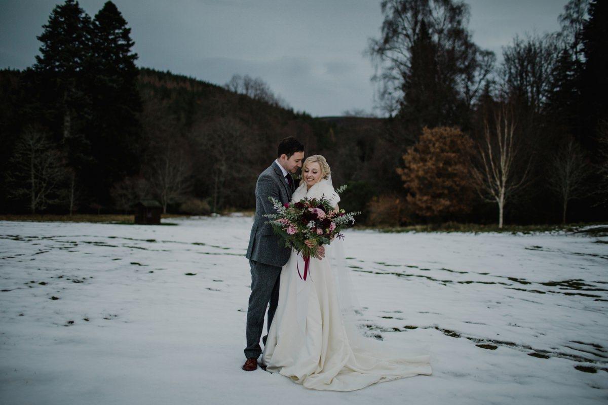 Snowy portrait of bride at groom at their winter wedding at Glen Tanar Ballroom