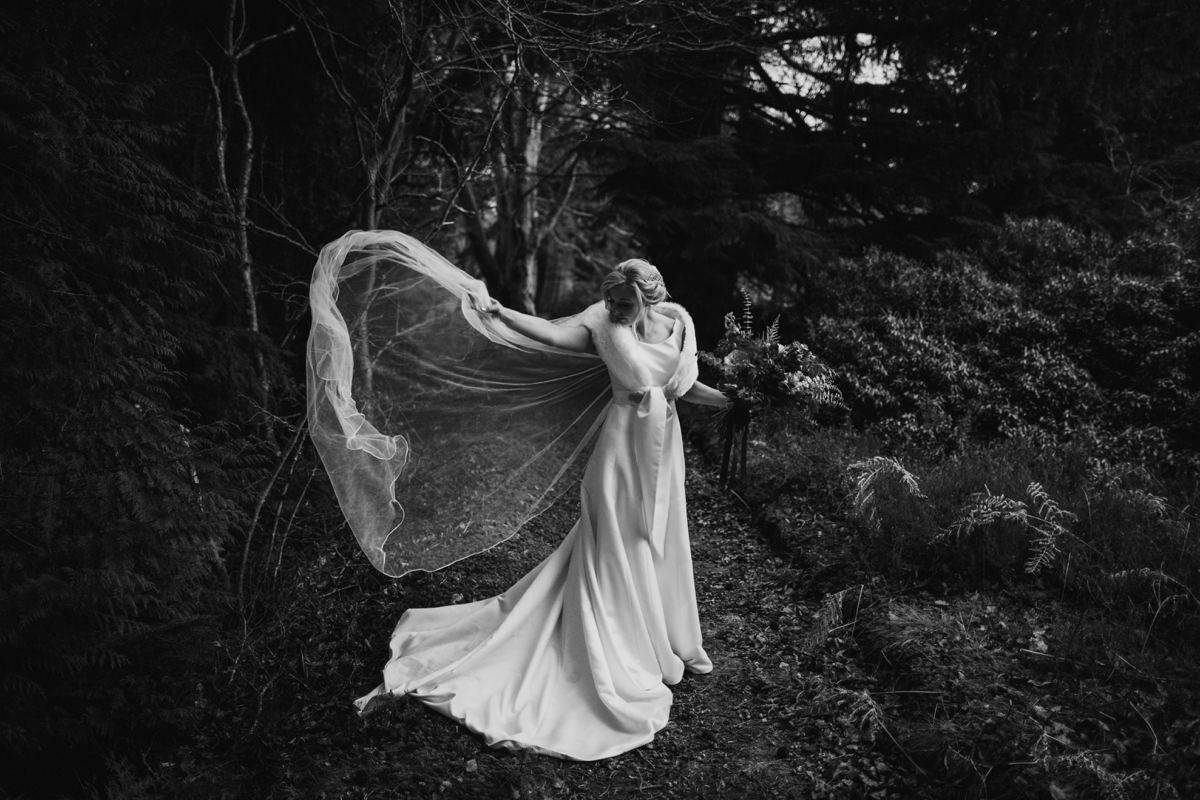 Black and white of bride adjusting her veil in the wind