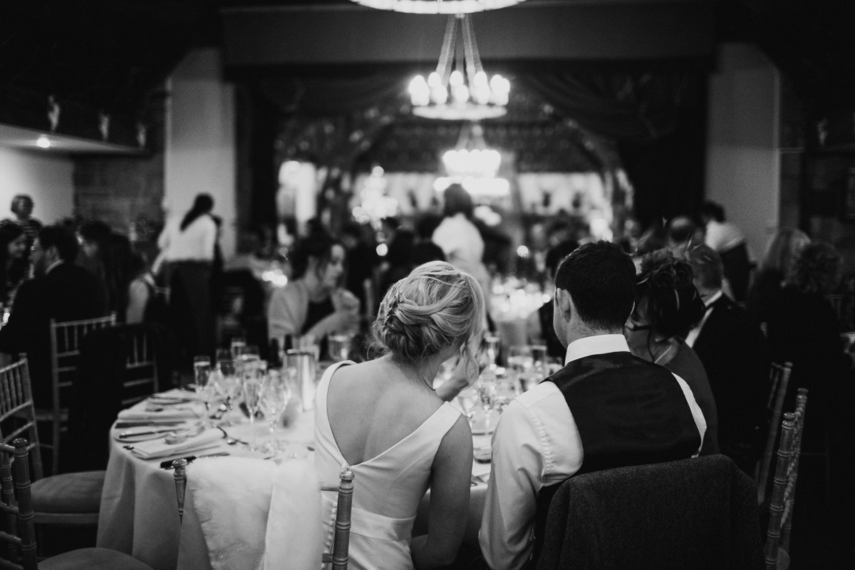 Black and white of wedding couple sat down for their meal