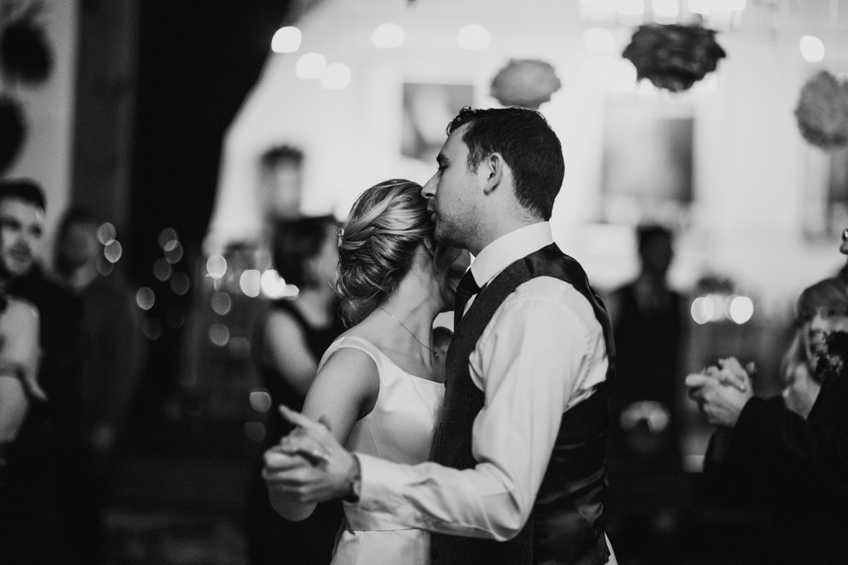 Black and white of bride and groom dancing their first dance
