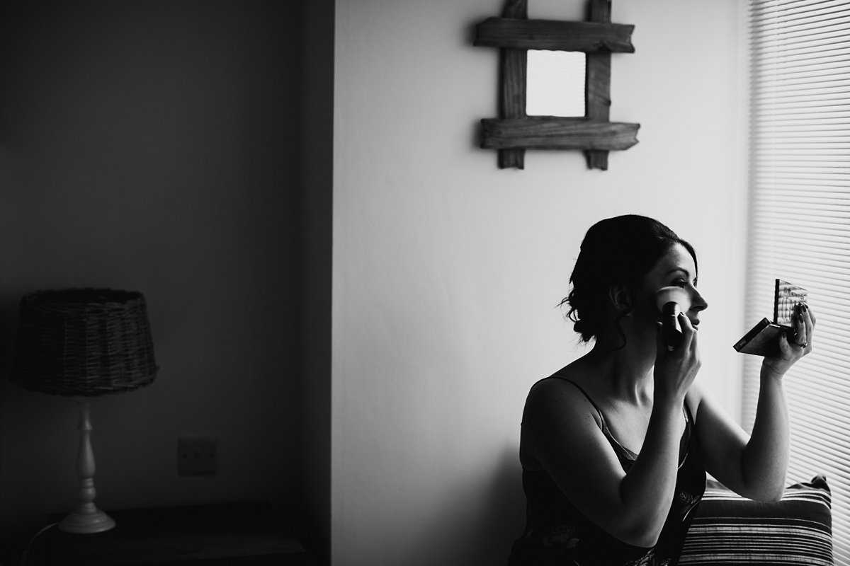 black and white of bride doing her makeup by the window