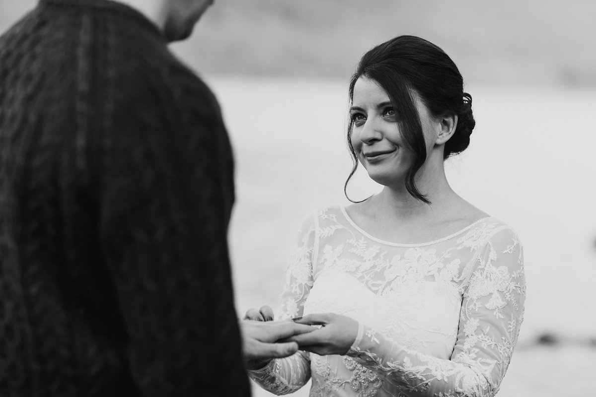 black and white of bride during exchange of rings