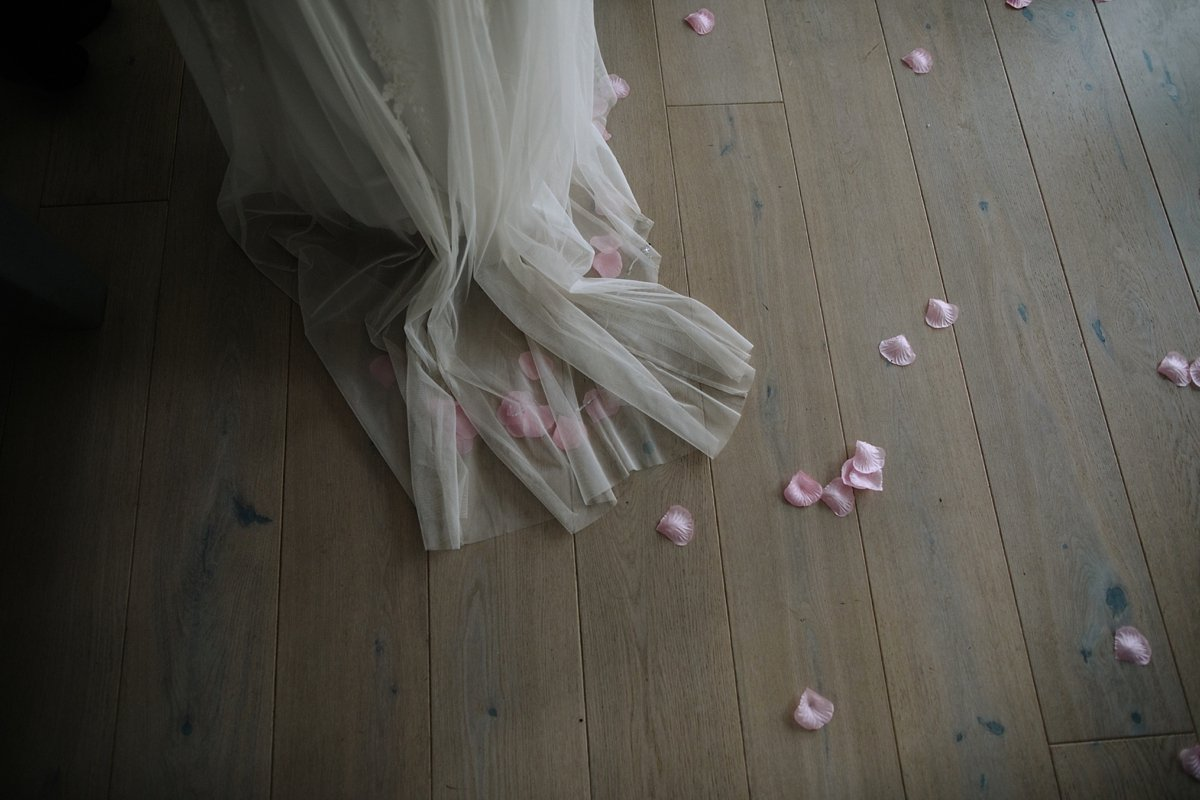 pink confetti on the floor next to bride's dress