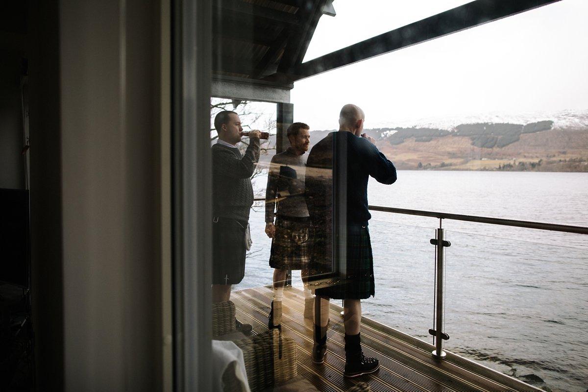 groom and groomsmen having a cigar on the balcony