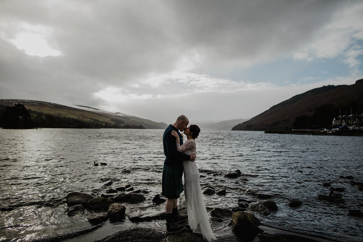 bride and groom kissing with views over loch tay