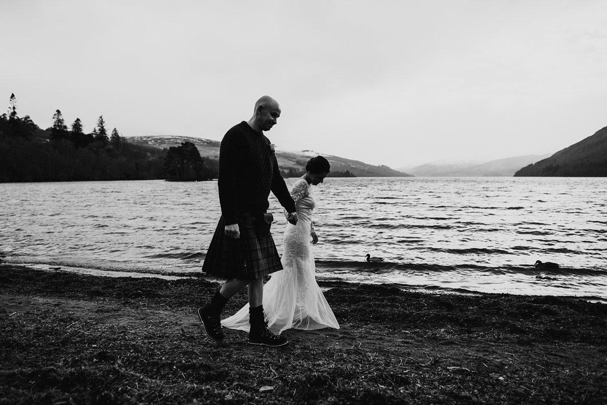 black and white of bride and groom walking by the loch