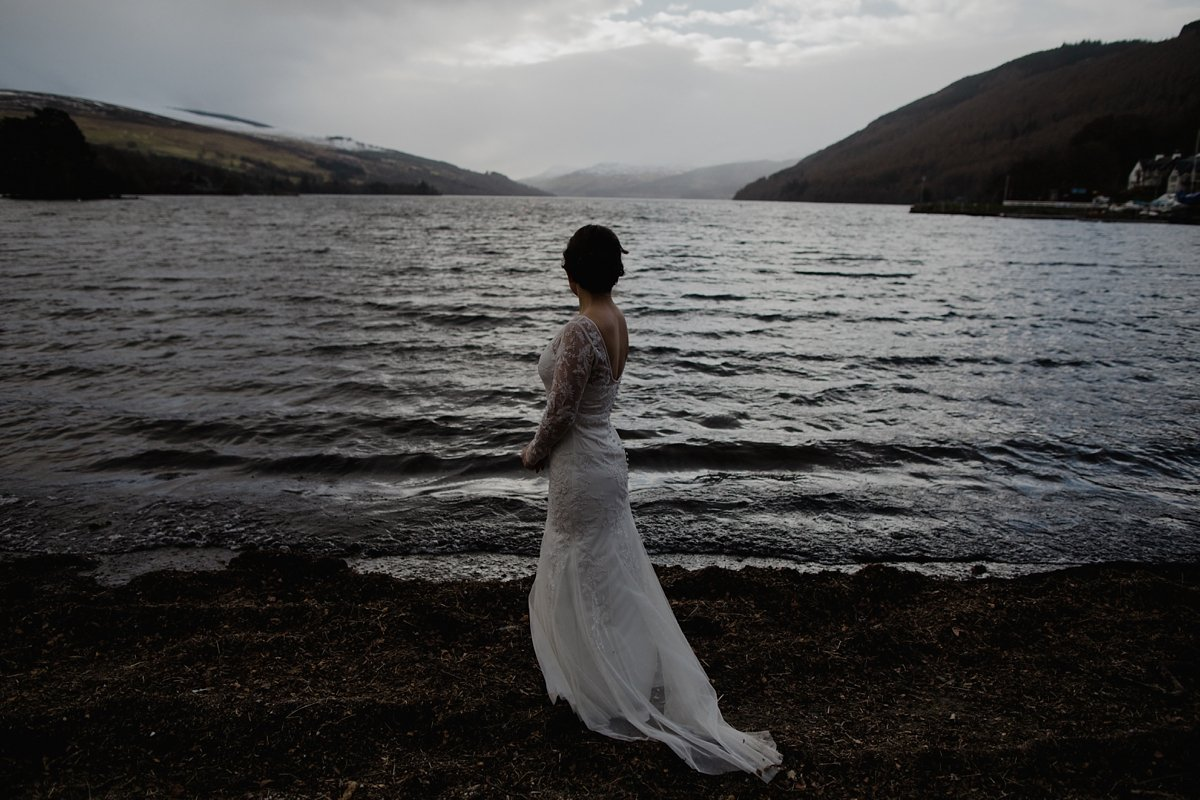 moody portrait of bride looking out over the water at loch tay