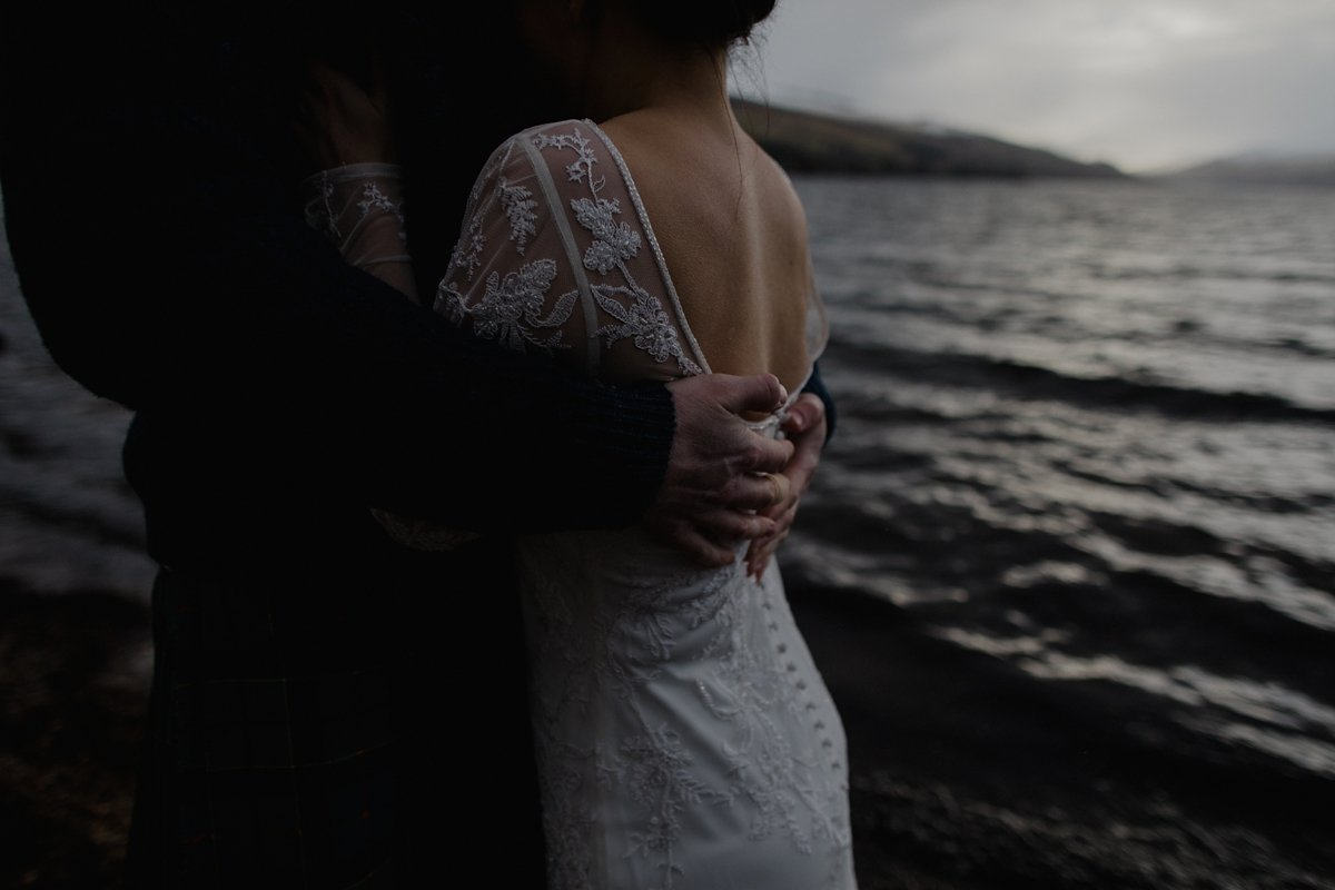 moody portrait of groom's hands wrapped around his bride with loch in background