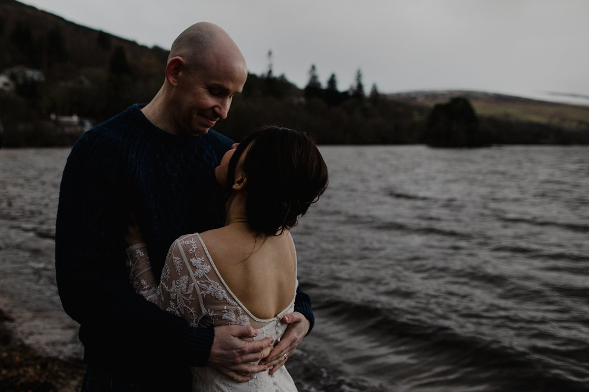 bride and groom hugging by the water