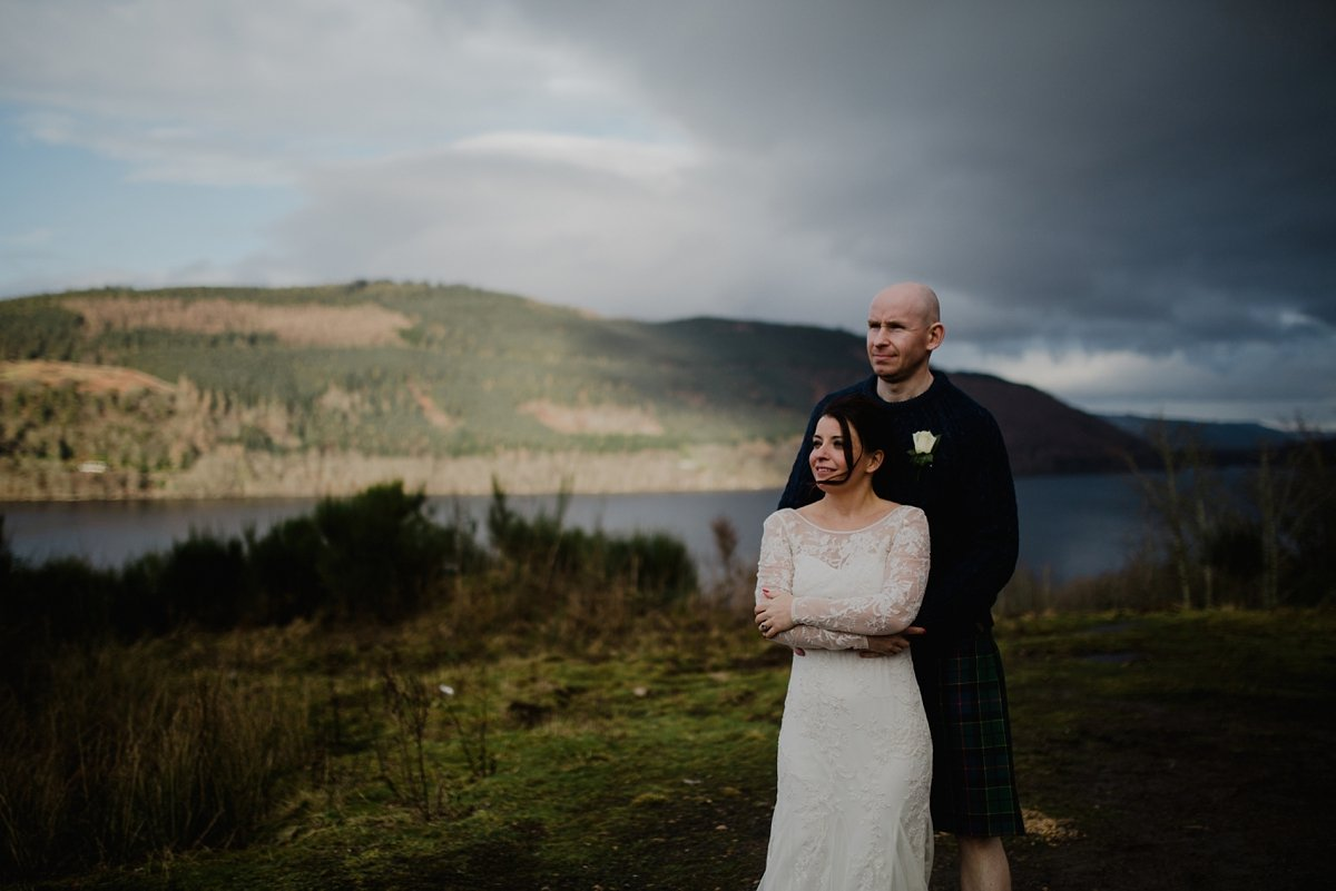 portrait of bride and groom above loch tay with golden light