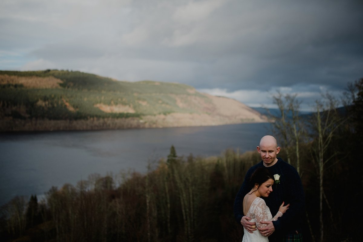 bride and groom with views high over loch tay at golden hour