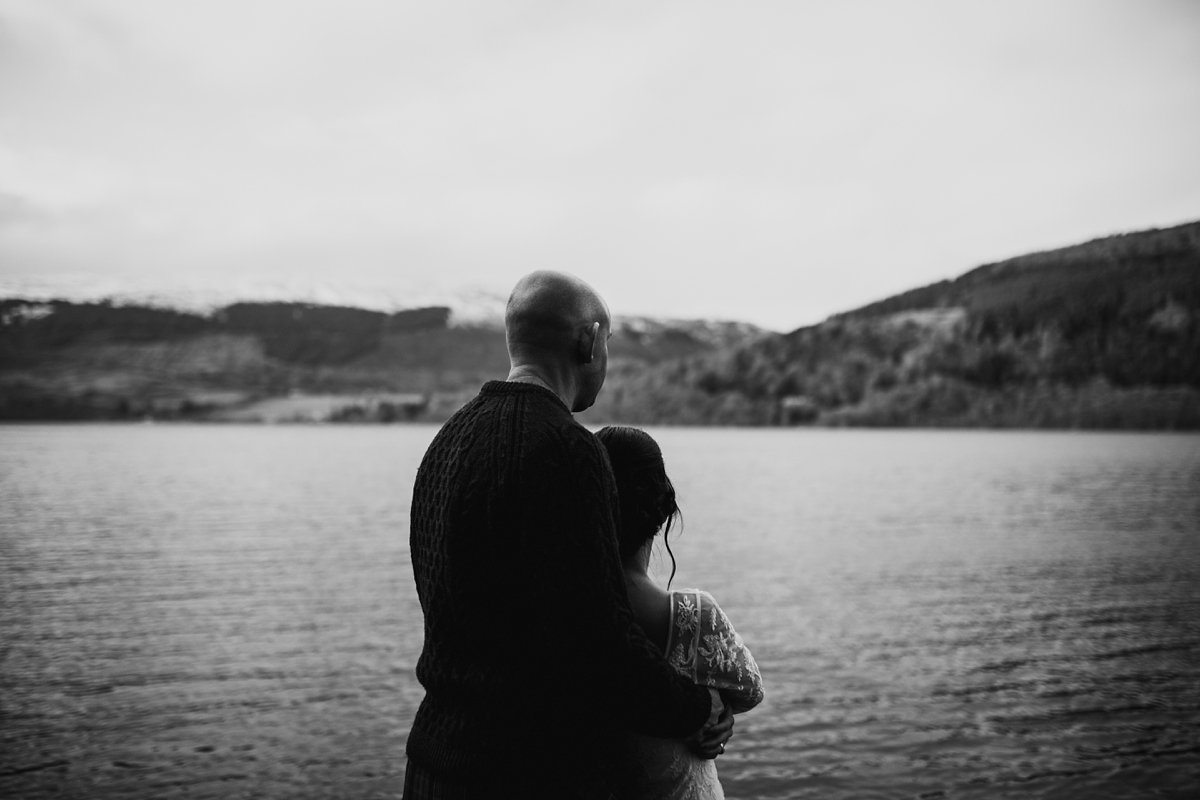 black and white of bride and groom looking over the water