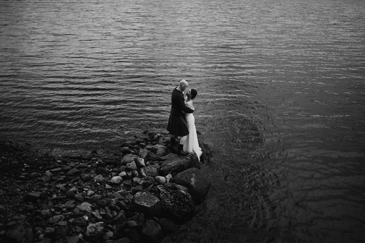 black and white portrait above bride and groom with water as backdrop