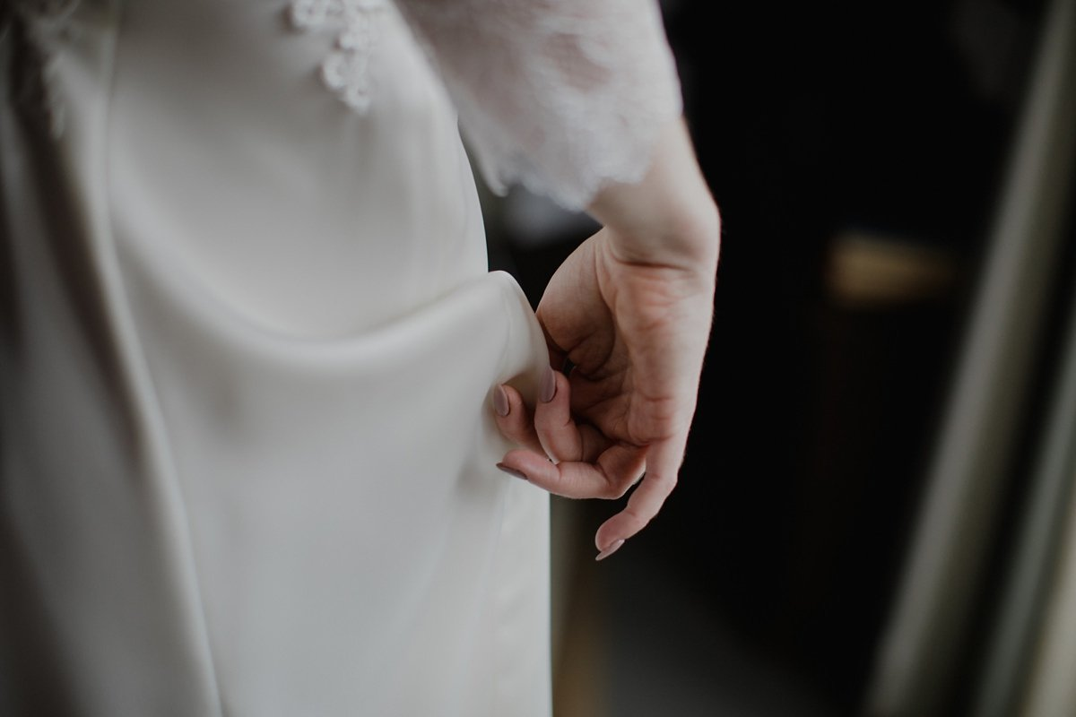 closeup detail of wedding dress, bride holding up dress