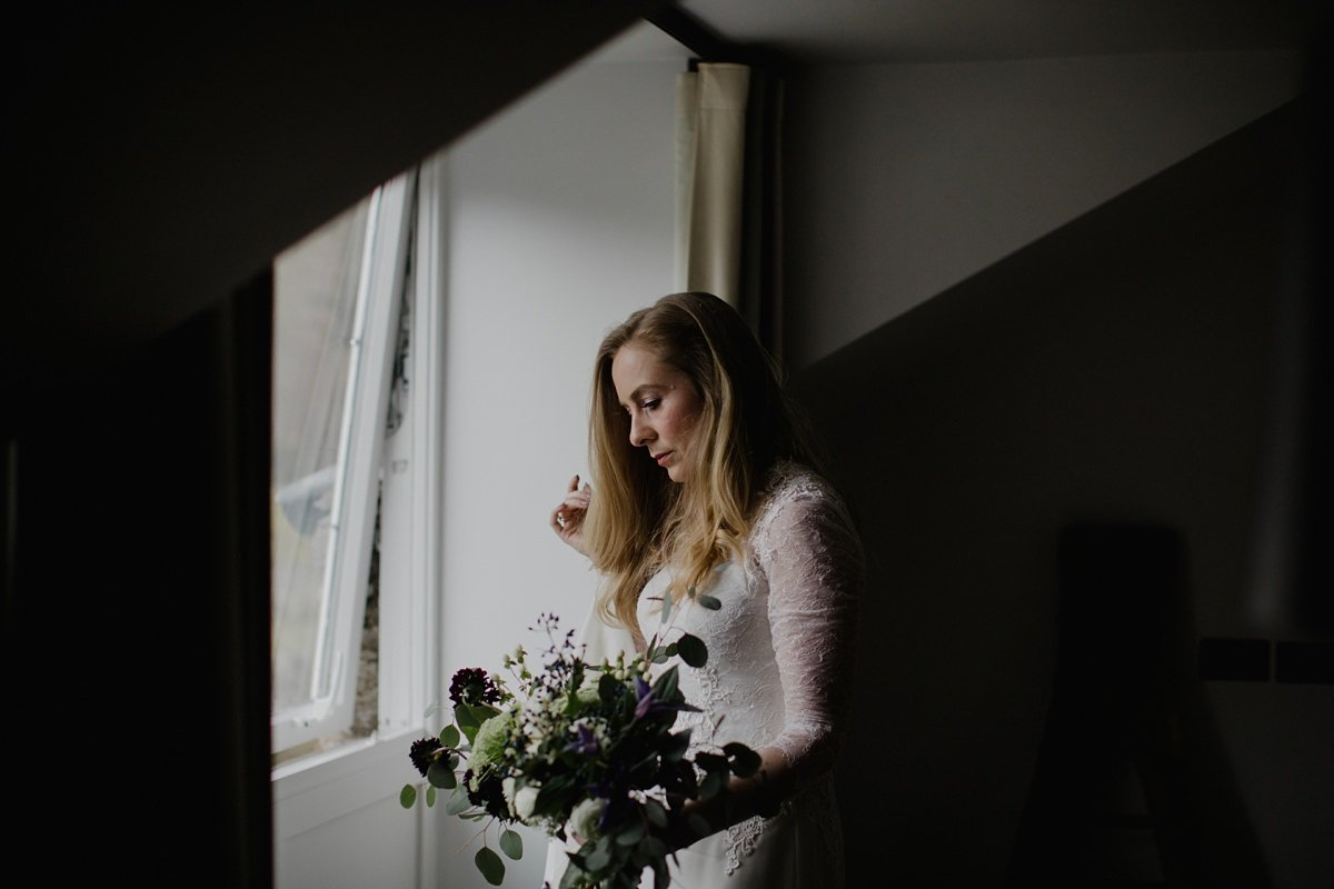 Bride taking a moment by the window before heading to the ceremony in her room at monachyle mhor