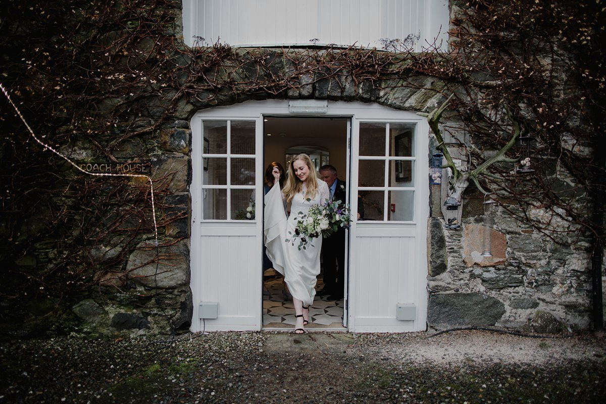 Bride smiling leaving her courtyard room at monachyle mhor to head to the ceremony