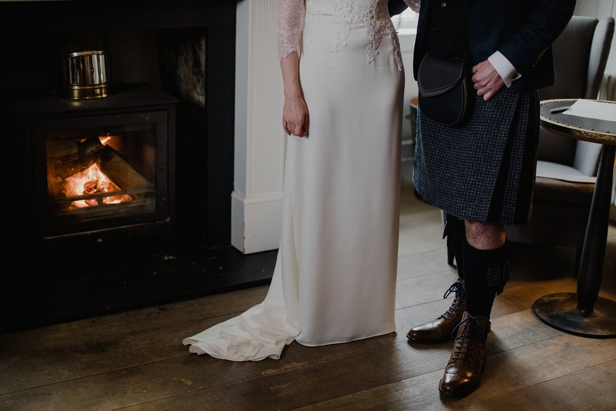 portrait from the waist down of Bride and groom side by side by the fire