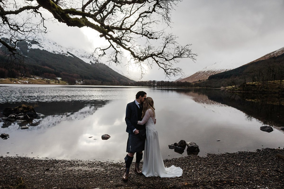 bride and groom portrait by the lochside framed by tree branch at monachyle mhor