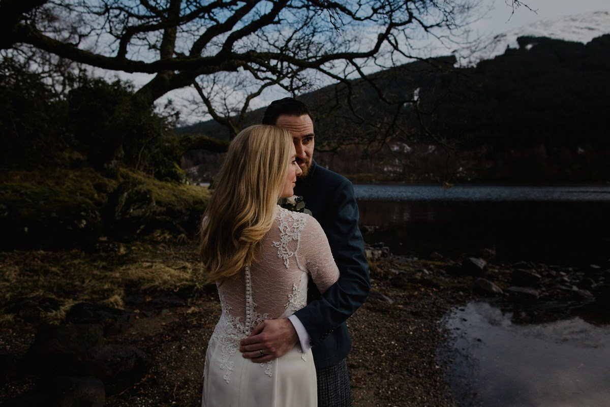 bride and groom embraced by the lochside, bride wears sheer back dress with lace and button detail