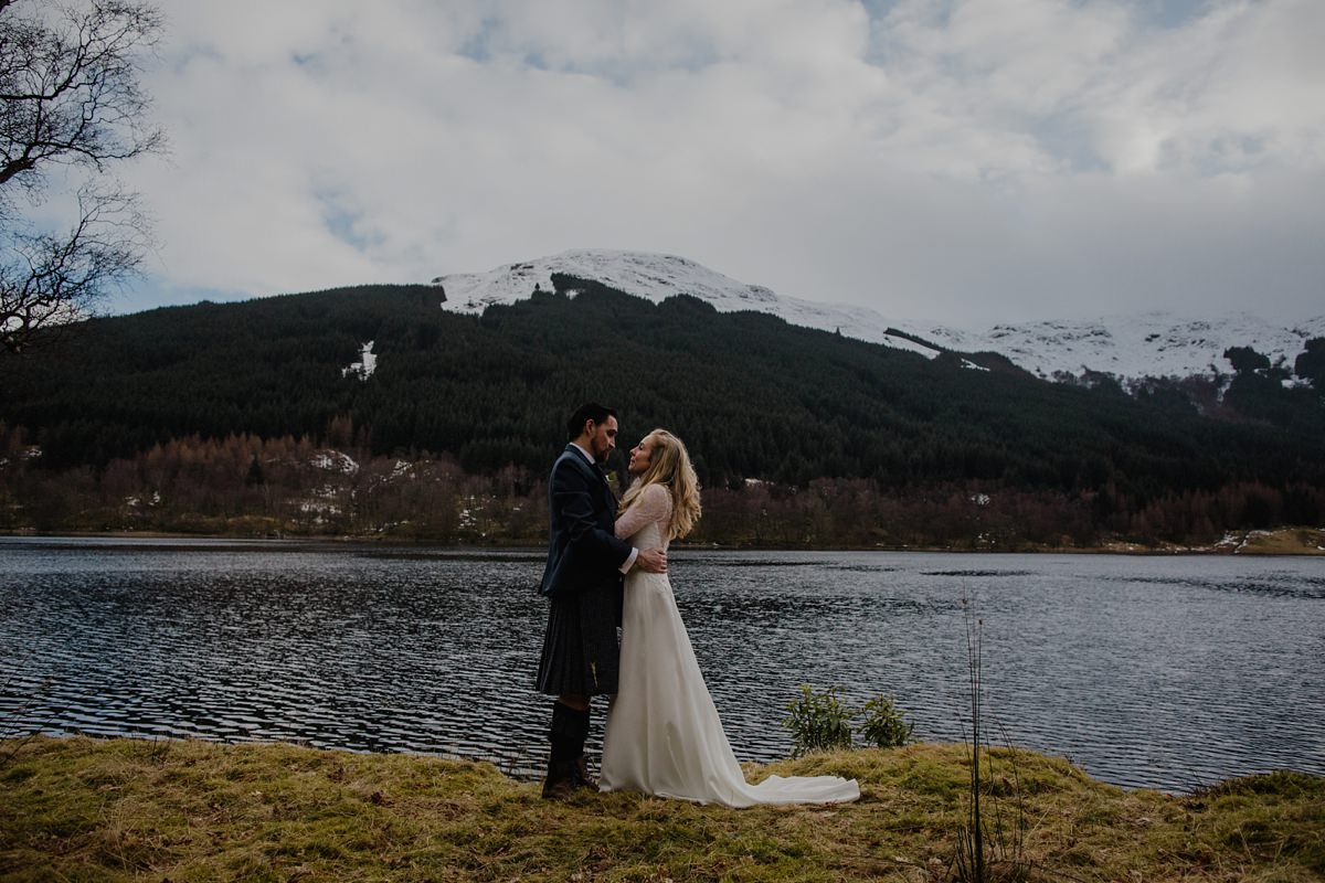 portrait of bride and groom with water and snow dusted hills behind