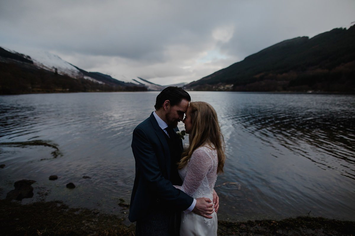 romantic, intimate, moody portrait of bride and groom by the lochside