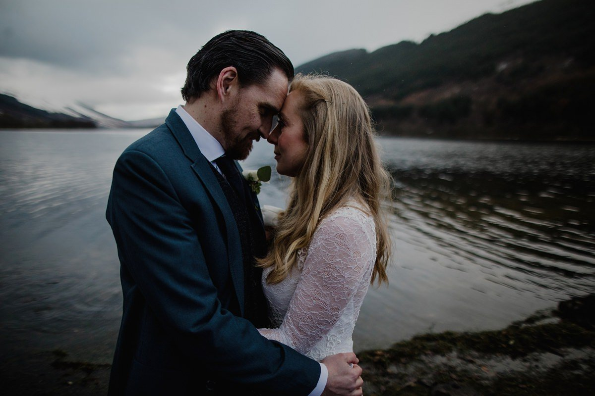 emotive, dark toned portrait of bride and groom by the lochside
