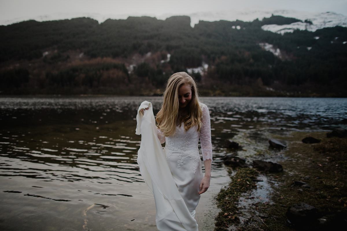 bride holding up her dress so doesn't get wet in the water, walking on the shore