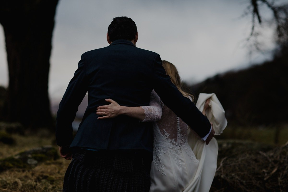 moody image of bride and groom walking together