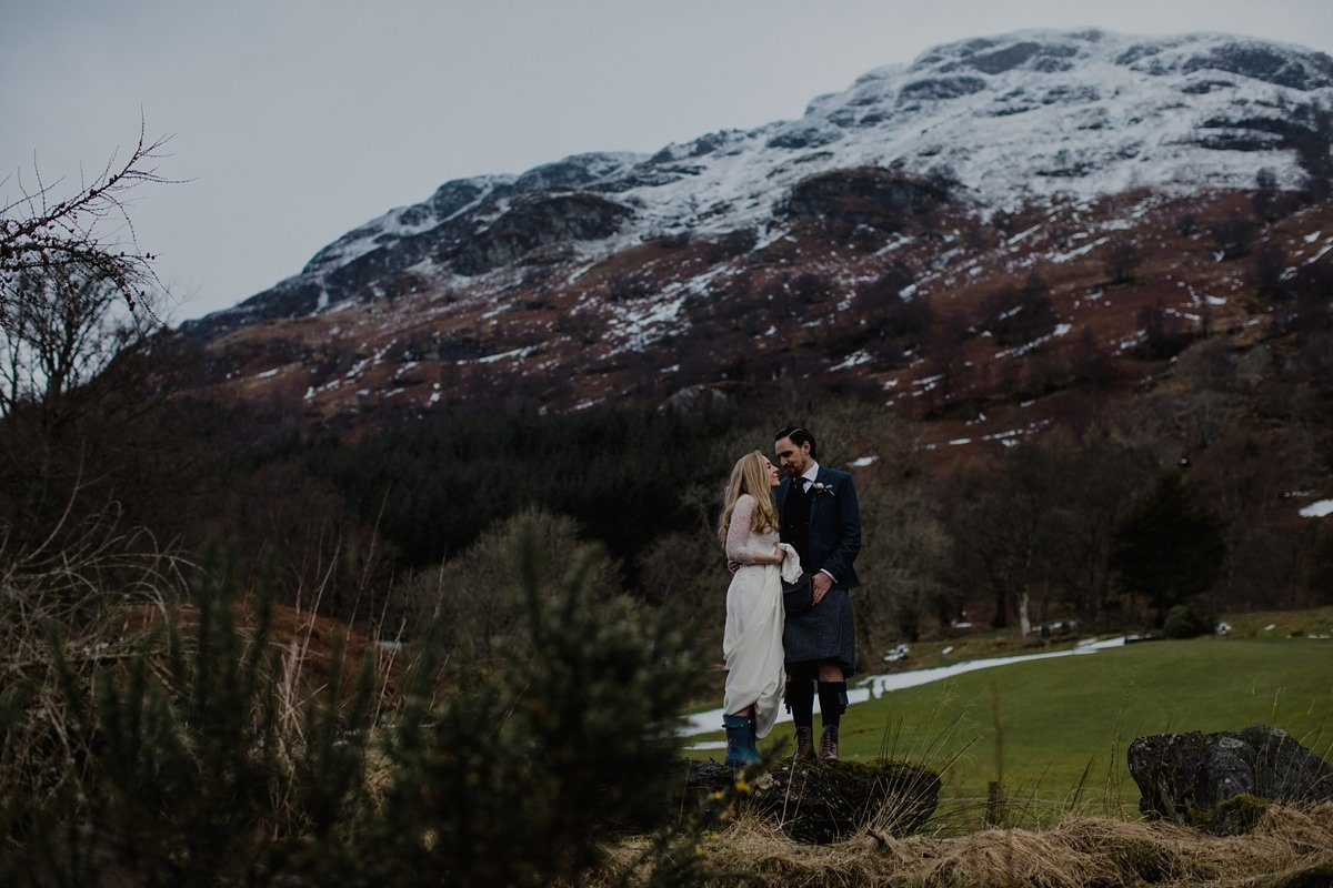 Portrait of bride and groom in front of the snow dusted trossachs hills at monachyle mhor