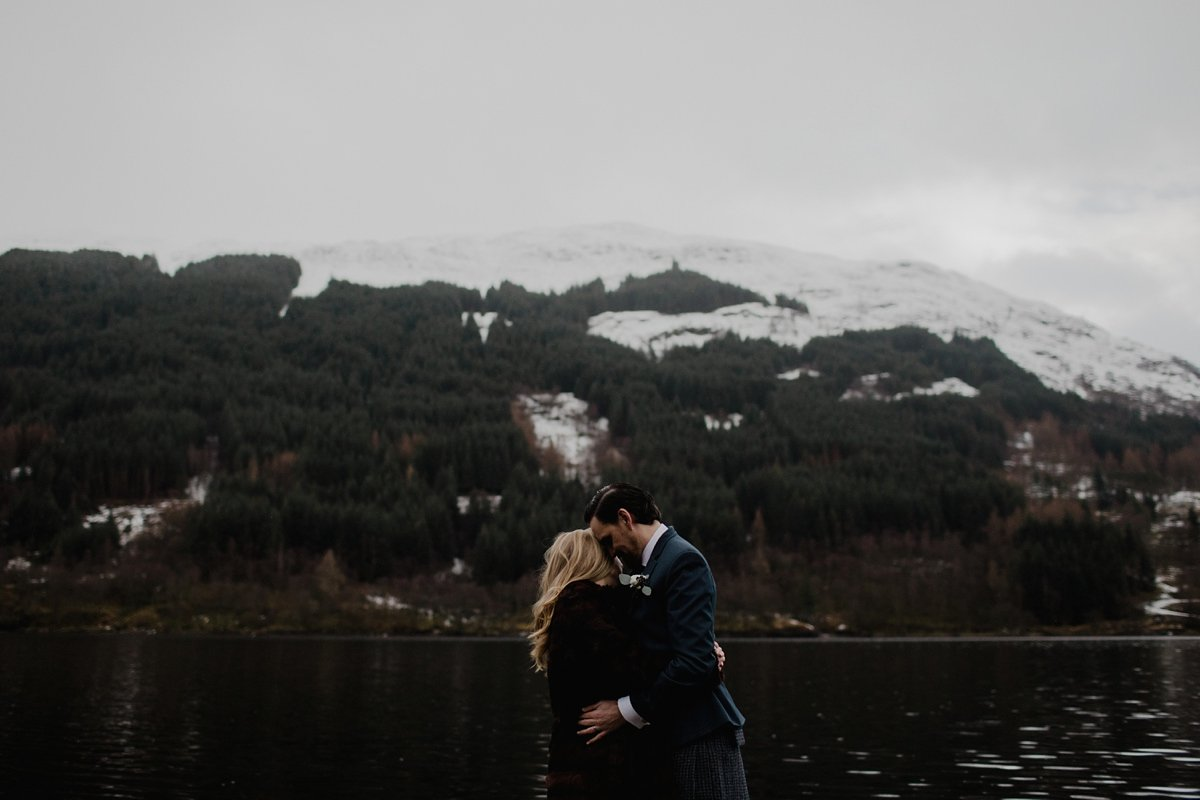 emotive portrait of bride and groom embraced by the winter lochside scene at monachyle mhor