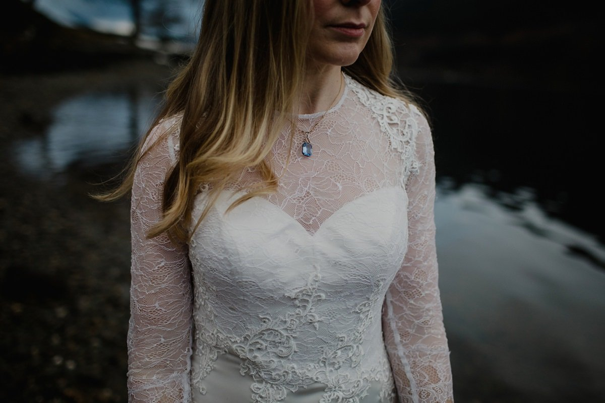 detail of bride's blue jewellery and lace detail on her dress
