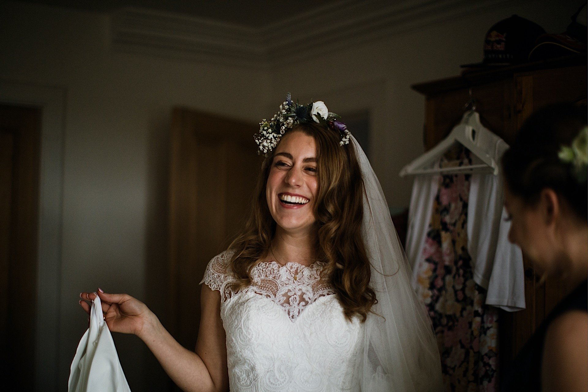 bride smiling wearing wedding dress and flowers in hair