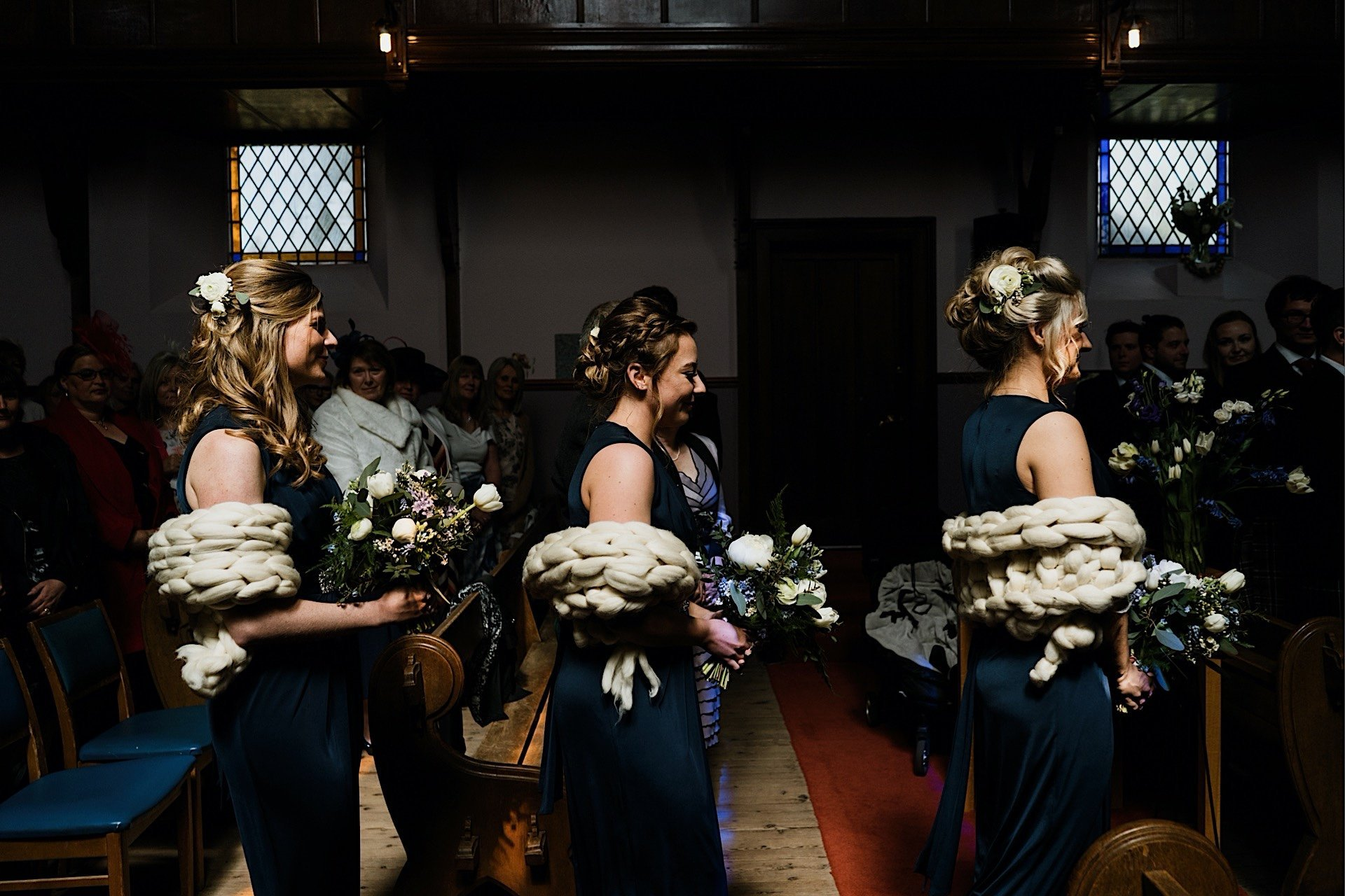 bridesmaids walking up the aisle wearing navy blue dresses and chunky knit ivory shawls